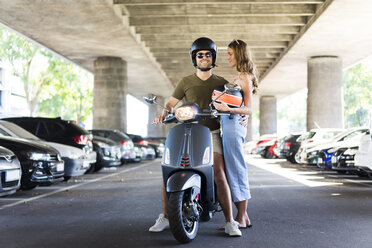 Happy couple with motor scooter at underpass - JOSF02607
