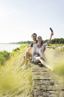 Happy couple at the riverside in summer taking a selfie - JOSF02616