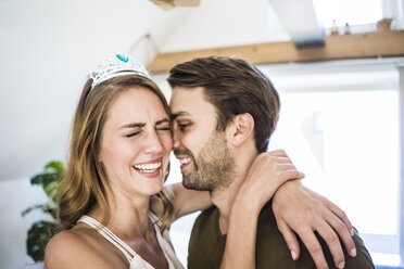 Happy couple at home with woman wearing tiara - JOSF02625