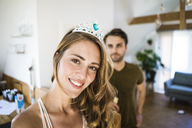Portrait of smiling woman wearing tiara at home with man in background - JOSF02628