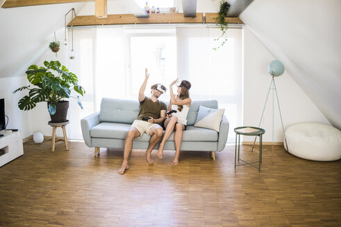 Happy couple sitting on couch at home wearing VR glasses high fiving - JOSF02634