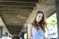 Portrait of smiling long-haired woman at underpass - JOSF02649