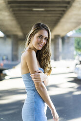 Portrait of smiling long-haired woman standing at underpass - JOSF02652