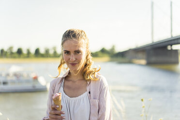 Portrait of smiling woman eating ice cream in summer at the riverside - JOSF02655
