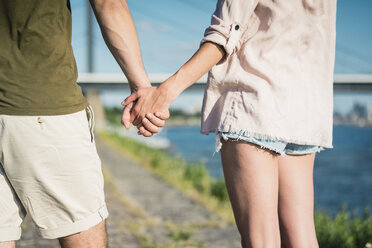 Close-up of couple hand in hand on waterfront promenade in summer - JOSF02658