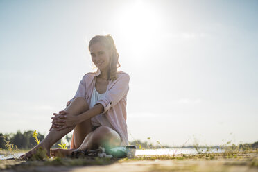 Portrait of smiling woman sitting at the riverside in summer - JOSF02667