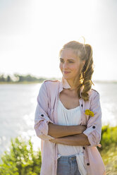 Portrait of smiling woman standing at the riverside in summer - JOSF02670