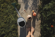 Three watering cans and woman's feet standing on garden path, top view - KMKF00440