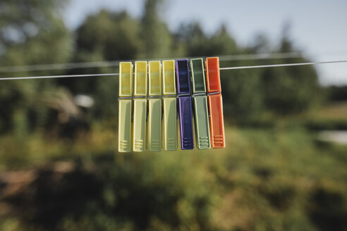 Row of clothes pegs hanging side by side on washing line - KMKF00443