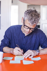 Mature man writing notepads on table  at home - TCF05806