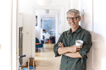 Portrait of smiling mature man with coffee cup leaning against door case at home - TCF05812