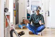 Mature man sitting on the floor at home using Virtual Reality Glasses - TCF05815