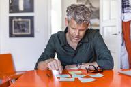 Mature man sitting at table at home looking at notepads - TCF05821