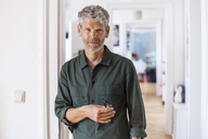 Portrait of mature man with grey hair and stubble at home - TCF05824