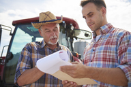 Two farmers discussing data from clipboard on the farm - ABIF00940