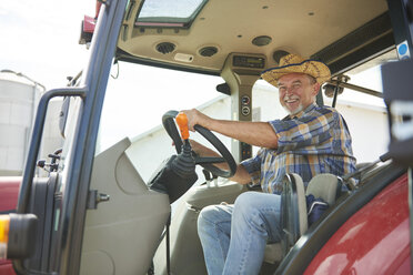 Portrait of smiling senior farmer on tractor - ABIF00943