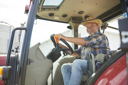 Portrait of smiling senior farmer on tractor - ABIF00943