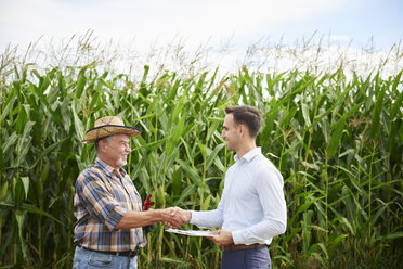 Farmer and businessman shaking hands at the cornfield - ABIF00949