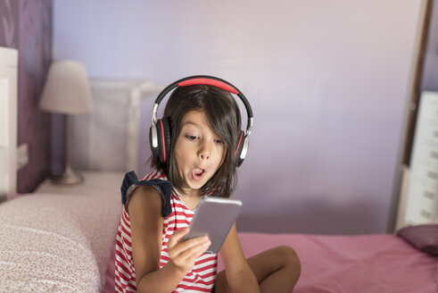Portrait of surprised little girl listening music with headphones and smartphone at home - JASF01926