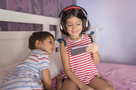 Little boy and his older sister sitting on bed at home looking at smartphone - JASF01929