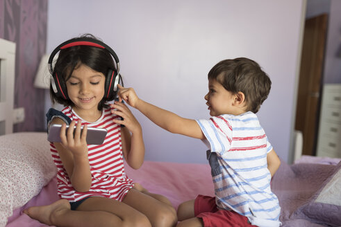 Portrait of smiling girl listening music with headphones while her little brother disturbing her - JASF01932