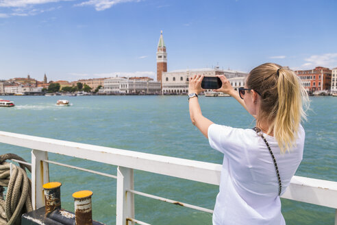 Italy, Venice, tourist taking a smartphone picture from the city - JUNF01207