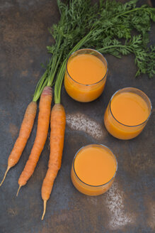 Three glasses of fresh carrot juice and three carrots - JUNF01231