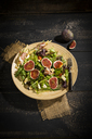 Mixed salad with figs, tomatoes, sheep cheese, grissini with ham on bambus plate - MAEF12732