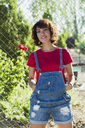 Portrait of smiling woman wearing jeans dungarees - KKAF01556