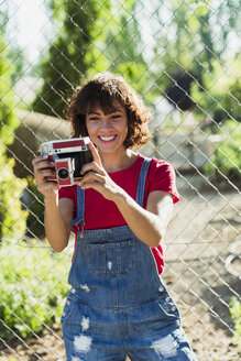 Portrait of smiling woman with instant camera - KKAF01559
