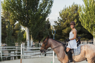 Smiling woman riding on horse - KKAF01580