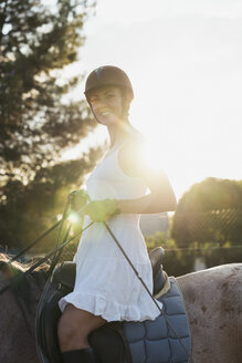 Portrait of smiling woman riding on horse at backlight - KKAF01583