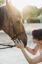 Smiling woman stroking horse - KKAF01586