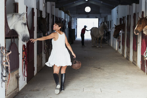 Smiling woman with riding helmet walking in stable - KKAF01592