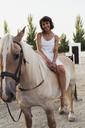 Portrait of happy woman sitting bareback on horse - KKAF01604