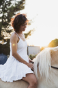 Smiling woman in white dress riding bareback on horse at sunset - KKAF01607