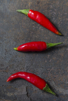 Three Red Chilli Peppers on rusty metal - JUNF01247
