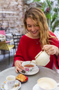 Smiling young woman pouring tea into a cup at pavement cafe - MGIF00237