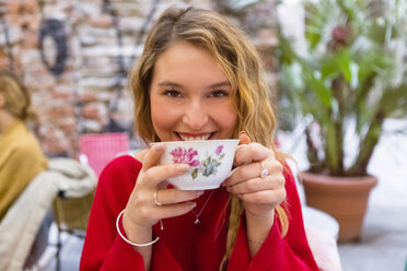 Portrait of smiling young woman drinking cup of tea at pavement cafe - MGIF00240