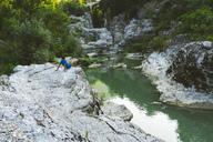 Italy, Marche, Fossombrone, Marmitte dei Giganti canyon, Metauro river, hiker sitting on riverside - LOMF00744