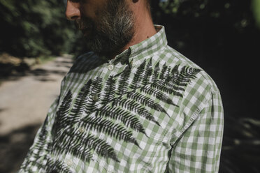 Shadow of fern leaf on man's shirt - KMKF00459