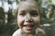 Portrait of smiling little girl with butterfly on her nose - KMKF00465