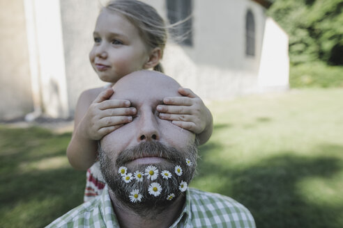 Little girl's hands covering eyes of mature man with daisies in his beard - KMKF00468