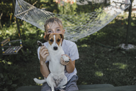 Boy sitting with Jack Russel Terrier on his lap in the garden - KMKF00483