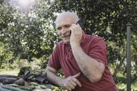 Portrait of smiling senior man on the phone in the garden - KMKF00492