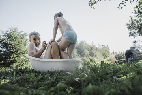 Brother and sister playing with water in little bath tub in garden - KMKF00495