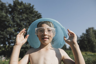 Wet boy wearing safety goggles holding bowl above his head in garden - KMKF00507