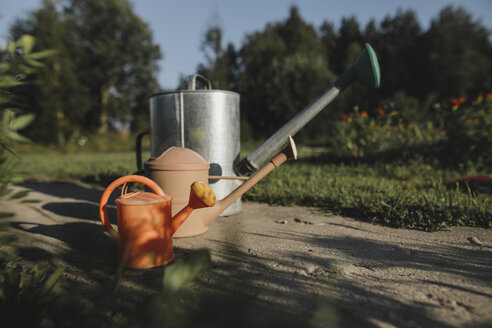 Variation of watering cans in garden - KMKF00513
