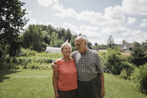 Happy senior couple standing in the garden - KMKF00515