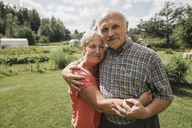Portrait of senior couple embracing each other in the garden - KMKF00518
